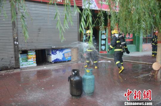 10日下午,山西太谷一饭店厨房失火,一具液化气罐被大火吞没烧成了黑色。消防官兵冒着生命危险冲进火海关闭阀门、拎出气罐,阻止了一起爆炸事故。 消防供图 摄
