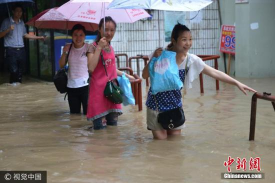 图为南京市雨花台区,市民在水中艰难出行。 文字来源:中国天气网 图片来源:视觉中国