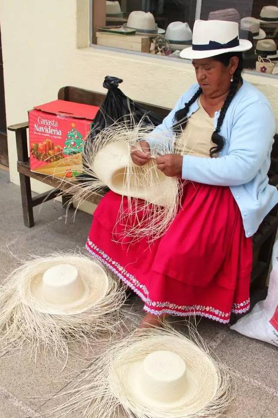 在厄瓜多尔昆卡老城,身着传统服饰的印第安妇女编织草帽。 (新华社记者梁君茜摄)
