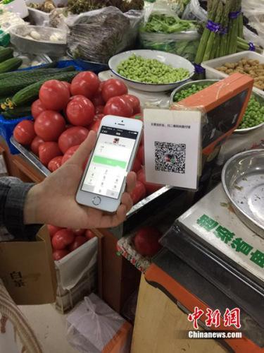 资料图:市民买菜时使用手机流量进行支付结账。中新网 吴涛 摄