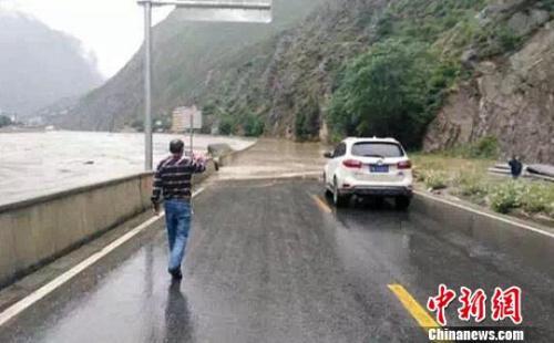 四川某地道路被淹没交通中断,过往路人和车辆通行受阻。 钟欣 摄