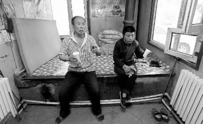 李得富向记者讲述自己的故事,患有智障的小女儿坐在身边 本组图片 新文化记者 王强 摄