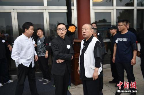 巩汉林与李建华在唐杰忠悲悼会现场。 中新网记者 金硕 摄