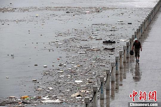 资料图:山西太原遭遇暴雨袭击,雨水将大量垃圾冲入汾河公园河道内,致使河面漂浮大面积垃圾,造成河水污染。中新社发 武俊杰 摄