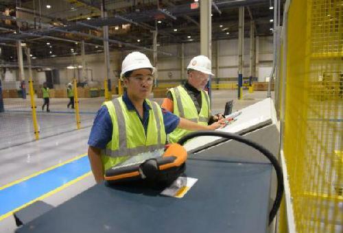 2015年8月,在美国俄亥俄州西南部的中国福耀玻璃团体莫雷恩工厂,中国工人倪正宏(左)和美国工人大卫·维格勒在一起事情。(资料图片)