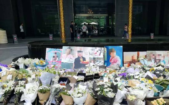 ▲6月29日下午,蓝色钱江小区入口处整齐地摆放着表示哀悼的白花(每经记者沈溦 摄)