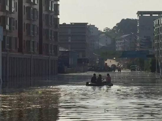 7月3日,梅树村民兵营长付晓光在积水中巡逻。新京报记者安钟汝 摄