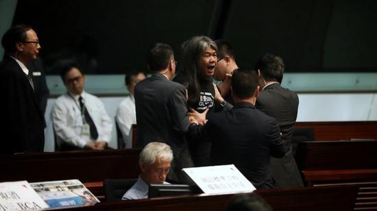 梁国雄被逐出会议厅。(图片来源:香港01)