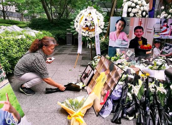 纵火悲剧发生后,各界人士纷纷送来鲜花悼念,遇难者朱小贞的母亲一直在女儿和孩子们的遗像前布置鲜花(于楚众摄)