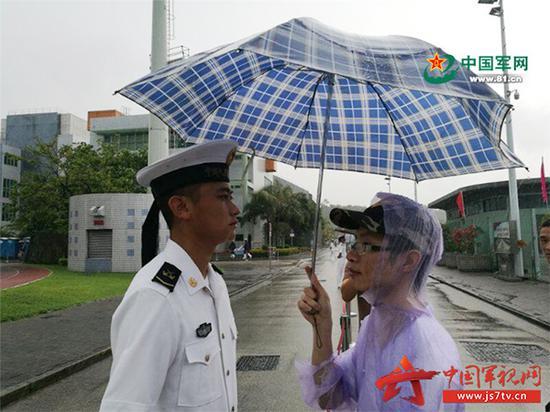 香港市民主动冒雨为战士撑伞挡雨。