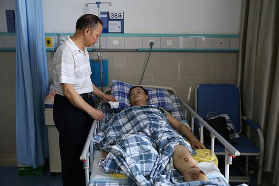 徐荣贵在病床前照顾儿子徐前凯。