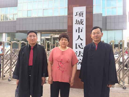 7月14日庭审前,李桂英和代理律师在法院门口合影。 家属供图