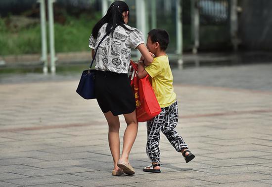 孩子紧紧抓着妈妈手,不让离开。