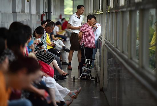 教室里孩子们正在上课,走廊上家长们静静地坐在椅子上刷手机或者小声聊着天。
