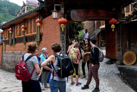 4月22日,外国游客在宁洱同心镇那柯里村观赏民居建筑。 新华社记者 杨宗友 摄