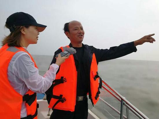记者在洪湖上采访。