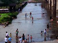 北京暴雨过后 莲石湖畔市民捉鱼忙