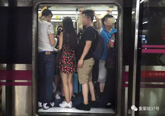 ▲地铁车厢内,被男乘客团团包围的女乘客。   新京报记者 大路 摄