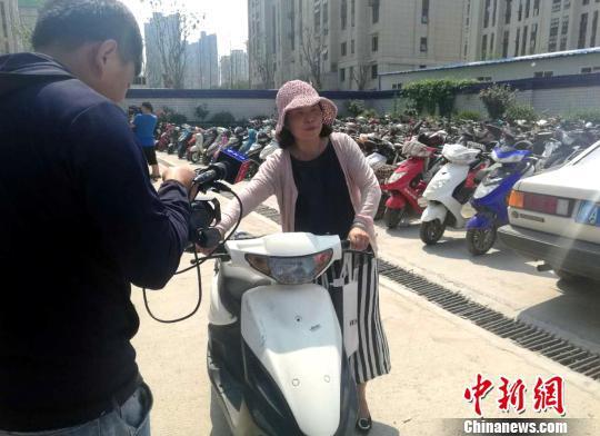图为一名女子领取丢失的电动车。 刘鹏 摄