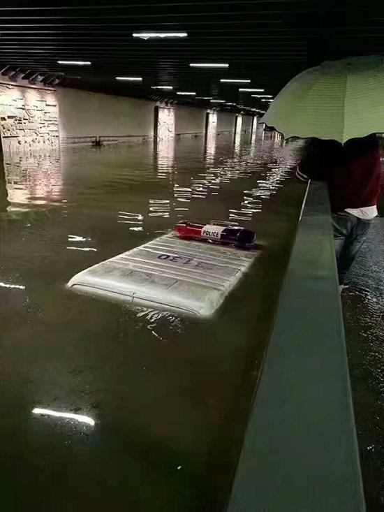 昆明北站隧道积水,一辆警车被水淹只露出车顶警灯部分。