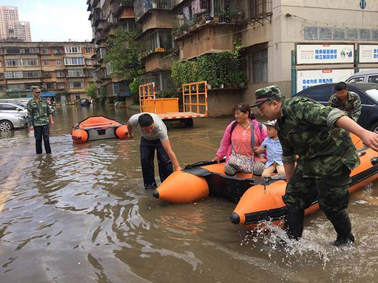 暴雨过后,积水困住市民,图为救援人员正在用皮划艇施救被困市民。