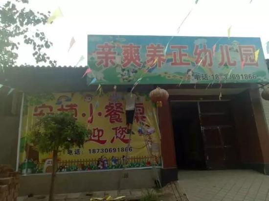 """在冯柳村,工人们正在将幼儿园门口""""亲爽养正""""的牌子换成""""安博幼儿园""""。新京报记者 高敏 摄"""