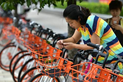 资料图片:一位市民在湖北省宣恩县摩拜单车投放现场扫描二维码取车。新华社发