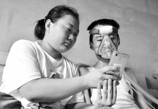 冀彦宇与妻子看着手机里孩子的照片