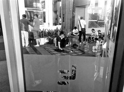 """多名讨债人在乐视大厦一层""""坐等"""",地上铺着野餐垫、瑜伽垫 供图/东方IC"""