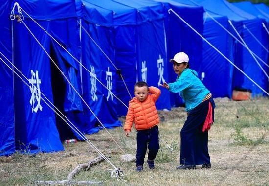 一对母子正在九寨沟景区荷叶寨的灾民安置点内。澎湃新闻记者 赵昀 图