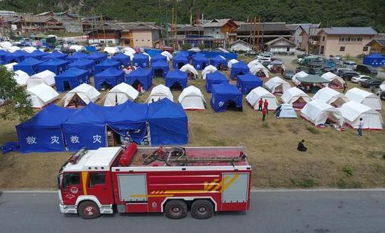 九寨沟景区荷叶寨的灾民安置点前,驻守着消防救援抢险车,随时应对安全救援任务。澎湃新闻记者 赵昀 图