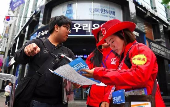 """▲资料图片:韩国首尔明洞商业区,两名旅游服务人员正为游客指路,其中一名戴有""""中国语""""标识。(法新社)"""