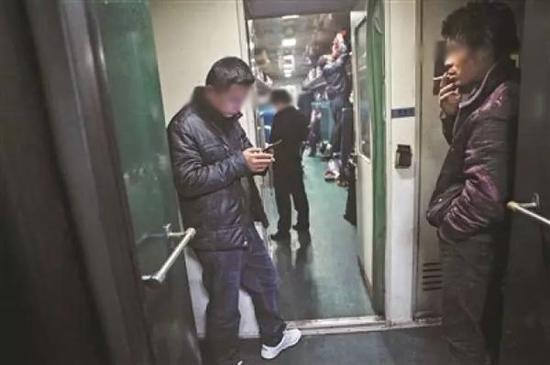 乘客在普通列车的车厢连接处抽烟。