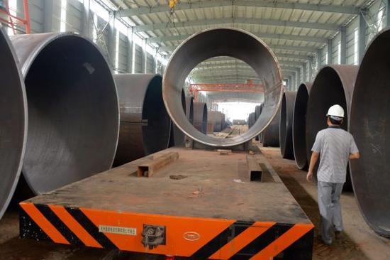 """资料图:2015年10月3日,这是在孟加拉国帕德玛大桥项目施工区域拍摄的一间厂房内的钢管(8月11日摄)。 由中国中铁大桥局中标承建的孟加拉国吉大港帕德玛大桥主桥长6150米,宽21.5米,是毗连中国与东南亚的""""泛亚铁路""""的主要通道之一,也是中国外洋中标的最大单体桥梁项目。新华社记者刘春涛摄"""