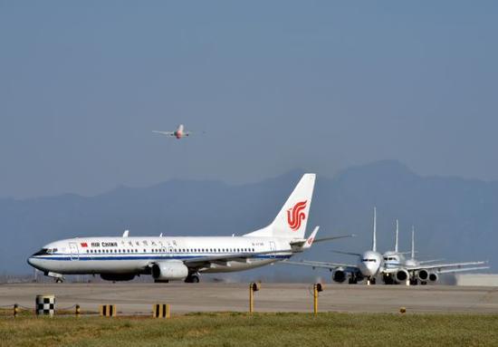 质料图片:飞机在北京都城机场中跑道高等候腾飞。