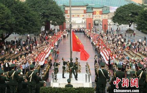 武警官兵升国旗,市民们行注目礼、高唱国歌。陈超 摄
