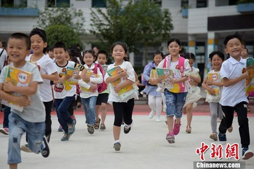 资料图:一年级的新同学怀抱新书本开心的走出教室,奔跑在校园里。中新社记者 张娅子 摄