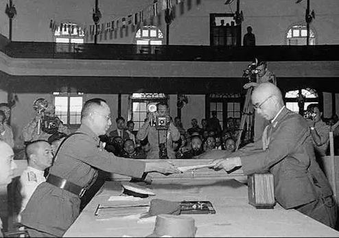 1945年9月9日,侵华日军最高批示官冈村宁次(右)在南京向中国陆军总司令何应钦递交降服佩服书。