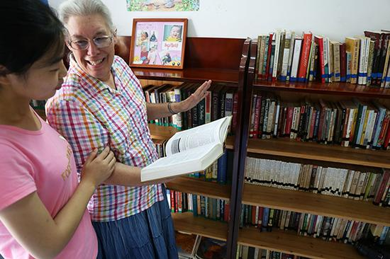 """2014年9月3日,埃斯特在""""客厅图书馆""""向学生介绍英文书籍。 江伟涛/视觉中国 资料图"""