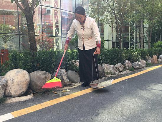 杨春梅在打扫天源酒店内的道路卫生。
