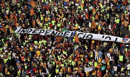 """在巴塞罗那9月11日的游行中,民众高举巨大""""独立""""横幅。(图片来源:路透社)"""