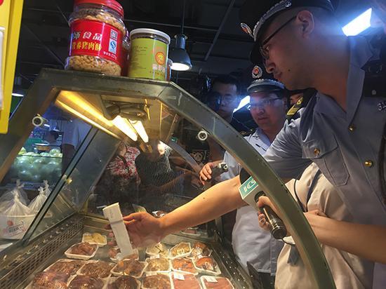 上海市食药监执法人员在家乐福超市熟食区检测储藏温度。 本文图片 澎湃新闻记者 陈伊萍 图
