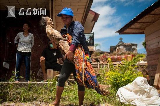 一名女子正抱着她亲人的遗体走过她家的农场