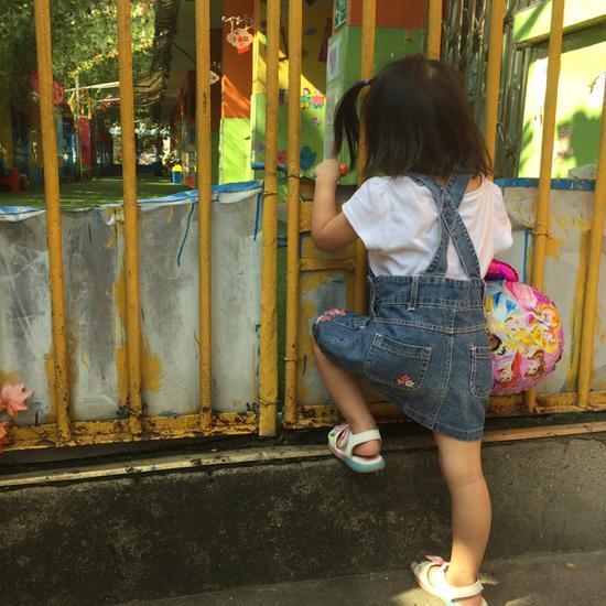 8月17日,依依在家附近的小火车幼儿园偏门张望。  澎湃新闻记者 朱莹实习生 张盼 图