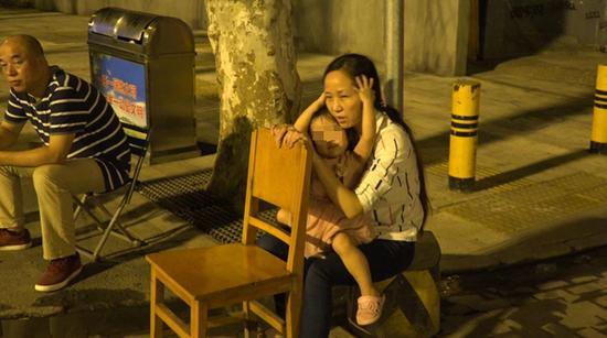 依依抱着妈妈的头,安慰她。 澎湃新闻记者 朱莹 图