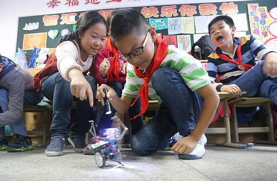 2016年5月16日,孩子们在公然课上学习机械人演出。