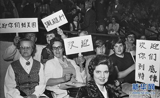 中、美两国乒乓球运发动在底特律举行角逐时,看台上底特律观众举着用中文写的口号牌,接待中国乒乓球代表团会见美国。 新华网 资料图