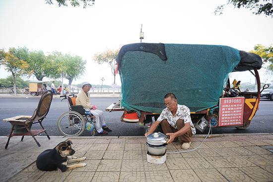 郭景新在路边做饭。崔光华 图