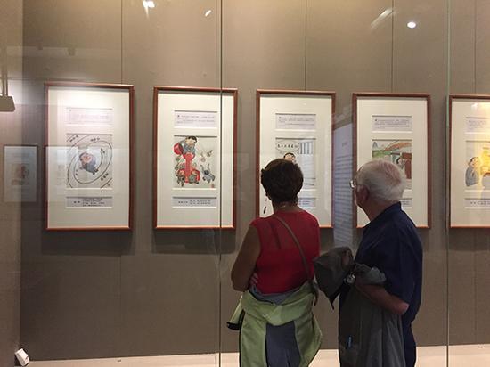 漫展吸引了两位外国游客,一旁有导游向他们诠释漫画主题。