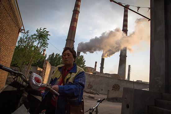 河北省邯郸市,村民经由一处工厂。有时间工厂排的烟遇上冬风,飘到村子里,都带着一股股硫酸味。视觉中国 资料